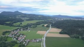 Cantidad aérea de un pueblo y un camino entre los campos y los bosques verdes en puesta del sol Montañas en horizonte metrajes