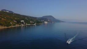 Cantidad aérea del abejón del barco de la velocidad que cruza en agua azul Montañas y mar en fondo Paisaje europeo Cámara metrajes