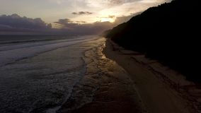 Cantidad aérea del abejón de las olas oceánicas que se rompen antes de la orilla en puesta del sol Bali, Indonesia