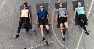 Cantidad aérea, del abejón del grupo de hombres bien entrenados y mujeres que hacen ejercicios metrajes
