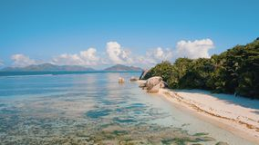 Cantidad aérea del abejón 4k Anse playa argent de la fuente de D tropical única 'en la isla de Digue del La, Seychelles almacen de metraje de vídeo