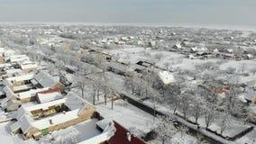 Cantidad aérea del abejón 4K del pueblo en el llano cubierto con nieve Tiempo nublado blanco del invierno almacen de video