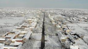 Cantidad aérea del abejón 4K del pueblo en el llano cubierto con nieve Tiempo nublado blanco del invierno almacen de metraje de vídeo