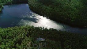 Cantidad aérea del abejón a través del campo al lago en el mediodía almacen de video