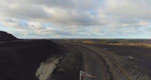 Cantidad aérea del camión rojo grande en una carrera de la explotación minera metrajes