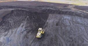 Cantidad aérea del camión rojo grande en una carrera de la explotación minera almacen de video