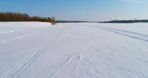 Cantidad aérea del paisaje del invierno de un río congelado con un bosque y de una vista de la ciudad con las fábricas Rastros de almacen de metraje de vídeo
