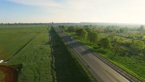 cantidad aérea 4K de los coches que montan en un camino entre los campos verdes en la subida del sol almacen de video