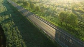 cantidad aérea 4K de un montar a caballo del coche en un camino entre los campos verdes en la subida del sol almacen de video