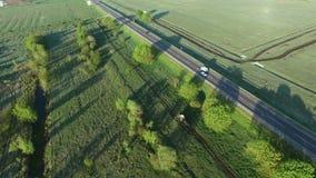 cantidad aérea 4K de un montar a caballo del tractor en un camino del campo a lo largo del camino del asfalt almacen de video