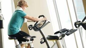 Cantidad acelerada de un hombre joven que se resuelve en la bicicleta estática en gimnasio almacen de metraje de vídeo