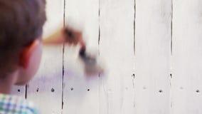 Cantidad acelerada de un muchacho que pinta la cerca de madera con el color blanco almacen de video