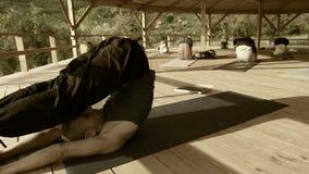 Cantidad baja de la saturación: el profesor de la yoga conduce un asana de ejecución del seminario almacen de metraje de vídeo