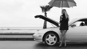 Cantidad blanco y negro de una mujer que se coloca debajo del paraguas cerca del auto quebrado
