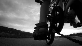 cantidad blanco y negro 4K de un muchacho que apresura su bicicleta almacen de metraje de vídeo