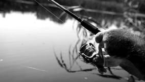 Cantidad blanco y negro: un hombre gira una bobina en los pescados de cogida de giro almacen de metraje de vídeo