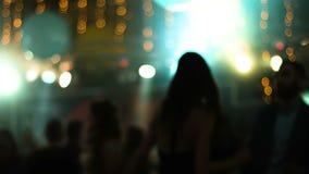 Cantidad borrosa con la gente atractiva joven que baila en un club nocturno Baile de la muchacha de nuevo a cámara almacen de metraje de vídeo