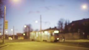 Cantidad borrosa del tráfico de ciudad de la noche con los coches, los peatones y la tranvía, tiro general metrajes