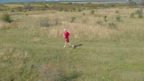 Cantidad a cámara lenta aérea de un hombre que corre en el prado húngaro