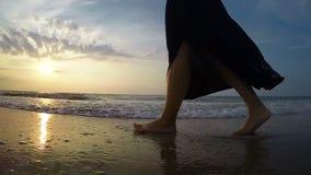 Cantidad a cámara lenta de los pies del ` un s de la mujer mientras que ella ` s que camina a lo largo de la costa almacen de metraje de vídeo