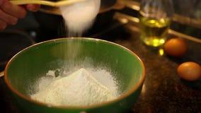 Cantidad a cámara lenta: un cocinero tamiza la harina de trigo antes de hacer la pasta metrajes