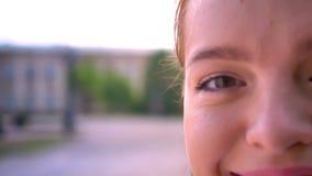 Cantidad cercana de la mitad de la cara feliz joven de la mujer del jengibre que mira la cámara y la sonrisa, de la calle en el f almacen de video