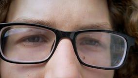 Cantidad cercana del hombre caucásico joven en la expresión de los ojos de vidrios, seria y concentrado metrajes