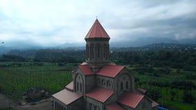 cantidad común aérea 4K de la catedral histórica, iglesia en la tarde debajo del cielo pesado azul en la región de Guria, Georgia almacen de metraje de vídeo