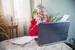 Cantidad de dinero impactante que una mujer mayor tiene que pagar sus cuentas fotografía de archivo