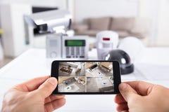 Cantidad de la cámara CCTV de Person Holding Mobile Phone With en la pantalla fotografía de archivo libre de regalías