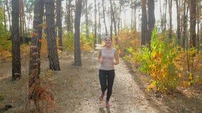 Cantidad de la cámara lenta de la mujer juguetona que corre en bosque hacia el sol almacen de metraje de vídeo