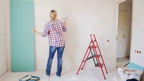 Cantidad de la cámara lenta del baile feliz de la mujer joven mientras que pinta la pared en su apartamento Chica joven que hace