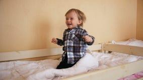 Cantidad de la cámara lenta del bebé de risa alegre que salta en el colchón en el dormitorio metrajes