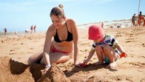 cantidad de la cámara lenta 4k de la madre joven hermosa que juega en la playa con sus 3 años del hijo del niño Familia que se re almacen de video