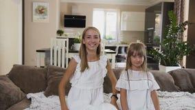 Cantidad de la cámara lenta de las dos hermanas felices de las adolescencias que caen en cama en la habitación Muchachas hermosas metrajes