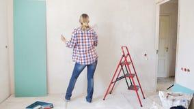 Cantidad de la c?mara lenta del baile feliz de la mujer joven mientras que pinta la pared en su apartamento Chica joven que hace