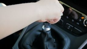 Cantidad de la c?mara lenta del primer de la mujer joven que conduce el coche con la caja de cambios manual Palanca de la caja de almacen de video