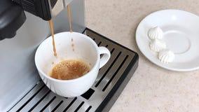 Cantidad de la c?mara lenta El café fresco de la máquina del café se vierte en la taza blanca Al lado de él es el platillo con lo almacen de video