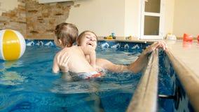 cantidad de la c?mara lenta 4k de la madre sonriente feliz que celebra a su ni?o y que lo lanza para arriba en aire en la piscina metrajes