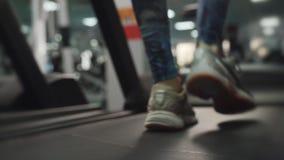 Cantidad de la c?mara lenta de piernas supuesto femeninas en las zapatillas de deporte que corren en la rueda de ardilla almacen de metraje de vídeo