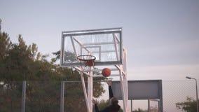 Cantidad de la parte trasera de un jugador de básquet de la chica joven que entrena y que ejercita al aire libre en la corte loca almacen de video