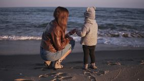 Cantidad de la parte trasera de una madre y de su niño contra el mar o el océano Poco, situación linda del bebé y mirada en el ag metrajes