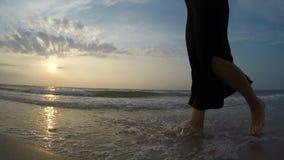 cantidad de la resolución 4K: piernas descalzas de caminar femenino joven en la playa de la puesta del sol almacen de metraje de vídeo