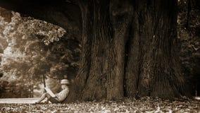 Cantidad de la sepia de un muchacho que se sienta en el pie de un árbol gigantesco y de una lectura almacen de video