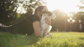 Cantidad de la vista lateral de una mujer caucásica joven en la camiseta negra que miente en la hierba con su pequeño perro y mir almacen de video