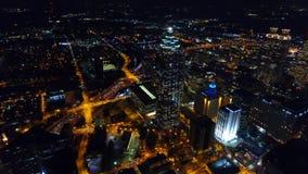 Cantidad de los edificios de Atlanta de la noche y de los semáforos de la autopista sin peaje, volando sobre céntrico, en tiemp almacen de video