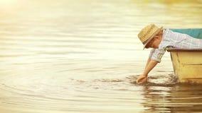 Cantidad de oro con gusto entonada: el muchacho pequenito en un sombrero de moda cuelga sus manos en el agua que está en el barco almacen de video