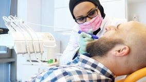 Cantidad de un dentista de sexo femenino en el hijab que trabaja en los dientes de los pacientes almacen de metraje de vídeo