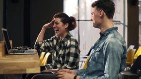 Cantidad de un par joven que ríe y que sonríe debido a somethng en su ordenador portátil Espacio dentro bien iluminado gasto metrajes