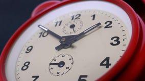 Cantidad de un reloj rojo viejo aislado en un fondo negro metrajes